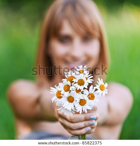 Young woman holding bouquet of camomiles. - stock photo