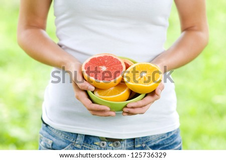 Young woman holding bowl filled oranges and grapefruits - stock photo