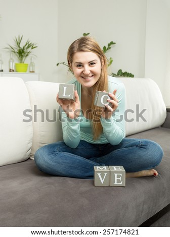"Young woman holding bricks with letters making word ""love"" - stock photo"