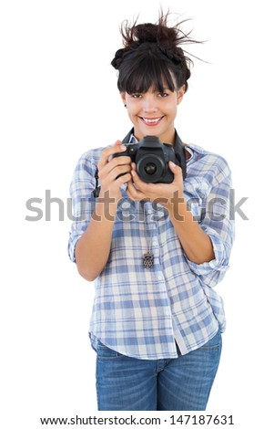 Young woman holding camera for taking picture on white background