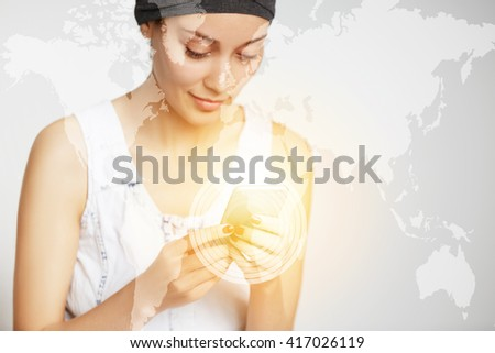 Young woman holding cell phone while messaging her boyfriend via social networks. Smiling girl using mobile phone, enjoying high-speed Internet connection at home. Worldwide connection interface icons - stock photo