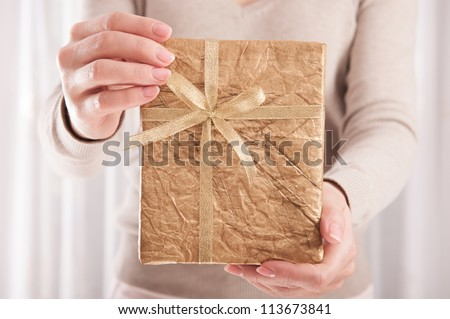 Young woman holding Christmas present box wrapped in golden paper - stock photo