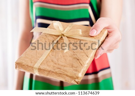 Young woman holding Christmas present box wrapped in golden paper