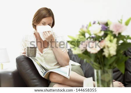 Young woman holding coffee cup and blowing nose with tissue paper on sofa - stock photo