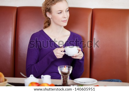 Young woman holding coffee cup while looking away in cafe - stock photo