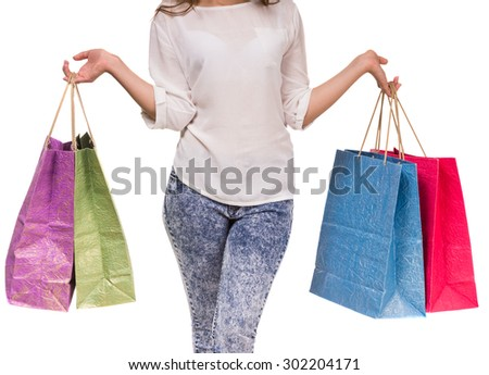 Young woman holding colored shopping bags in two hands on white background. Close-up.