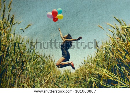 Young woman holding colorful balloons and flying over a meadow.  Photo in old color image style. - stock photo