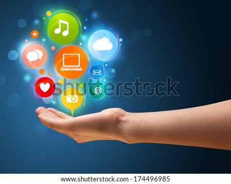 Young woman holding colorful multimedia icons in her hand - stock photo