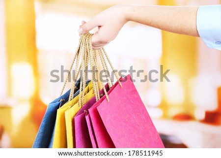 Young woman holding colorful shopping bags in  her hand, on bright background - stock photo