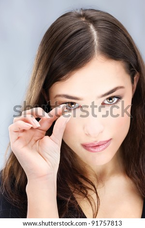 Young woman holding contact lens with two fingers in front of her eye - stock photo