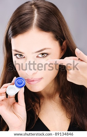 Young woman holding contact lenses cases and lens in front of her face - stock photo