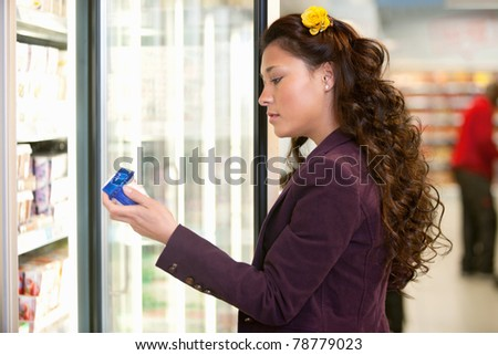 Young woman holding container in front of refrigerator in the supermarket - stock photo