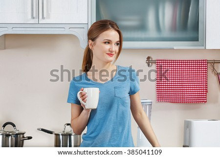Young woman holding cup in the kitchen