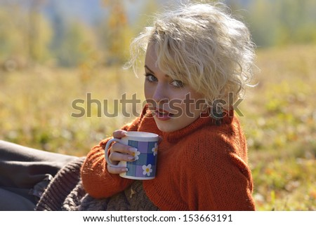 Young woman holding cup of tea outdoor - stock photo