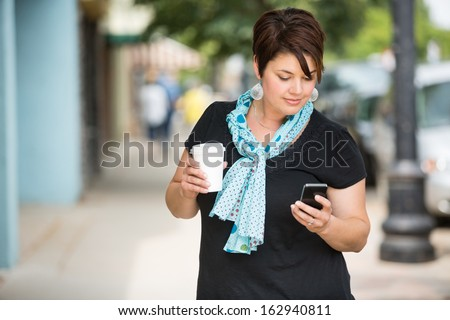 Young woman holding disposable coffee cup while text messaging through smartphone outdoors - stock photo