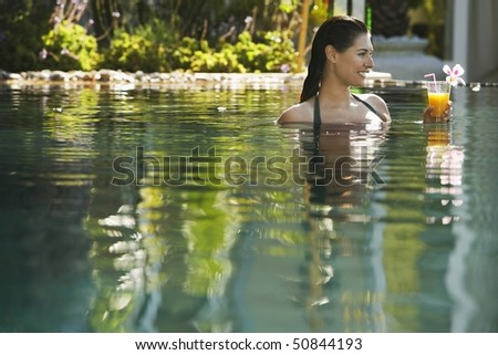 Young woman holding drink in natural swimming pool, portrait - stock photo