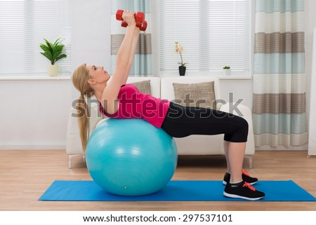 Young Woman Holding Dumbbell While Exercising On Fitness Ball In Living Room
