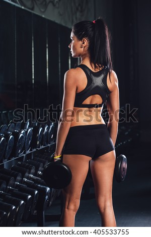 Young woman holding dumbbells in gym - stock photo