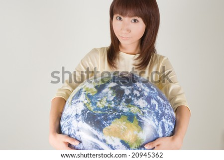 Young woman holding earth ball