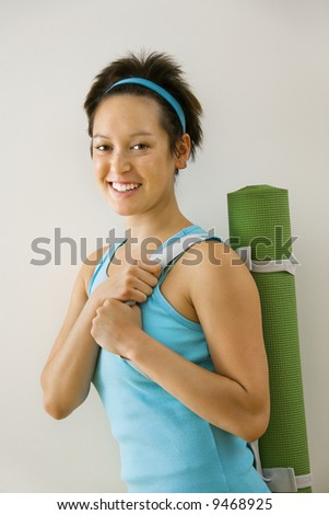 Young woman holding exercise mat and smiling. - stock photo