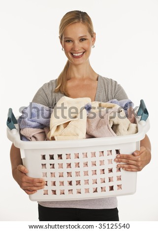 young woman holding filled laundry basket on white seamless background