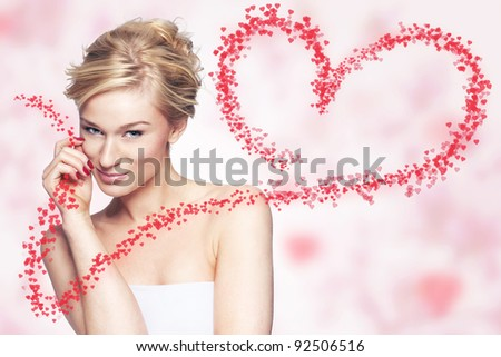 Young woman holding flying hearts on pink background