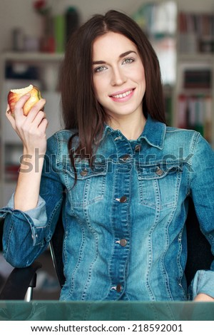 Young woman holding fresh apple in office - stock photo