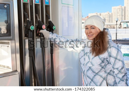 Young woman holding fueling nozzle at petroleum station at winter - stock photo