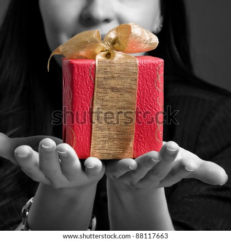 Young woman holding gift against dark background. Black-white image - stock photo