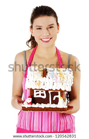 Young woman holding gingerbread house model, isolated on white background