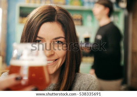 Young woman holding glass of beer with man serving in the background