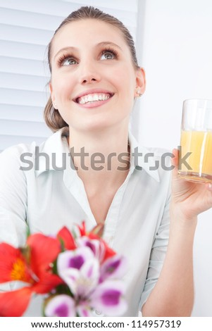 Young woman holding glass of juice, dreaming.