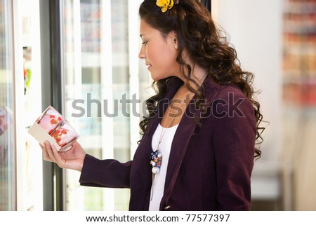 Young woman holding goods from a cooler in the supermarket - stock photo