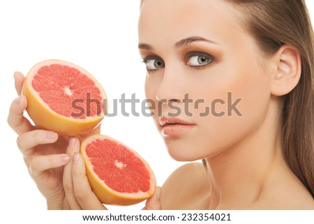 Young woman holding grapefruits.