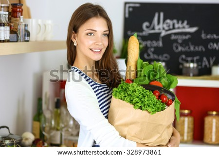 Young woman holding grocery shopping bag with vegetables  - stock photo
