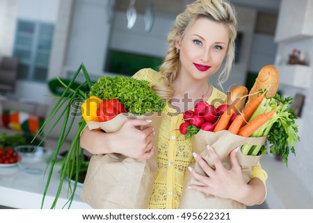 Young woman holding grocery shopping bag with vegetables. Happy young housewife with shopping bag full of vegetables. kitchen Cooking healthy Food. Diet Concept