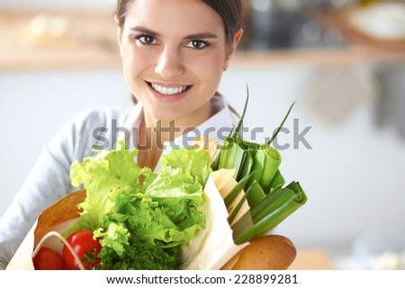 Young woman holding grocery shopping bag with vegetables Standing in the kitchen. - stock photo