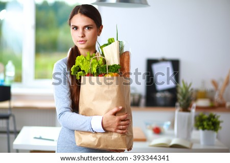 Young woman holding grocery shopping bag with vegetables .Standing in the kitchen - stock photo