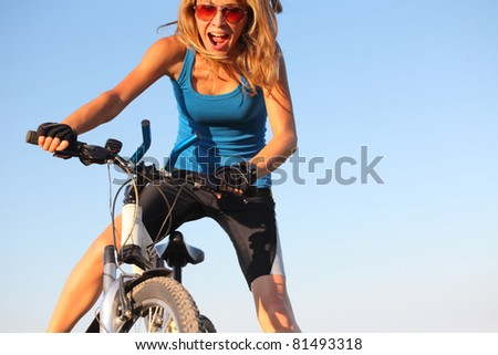 Young woman holding handlebar of a bicycle and shouting - stock photo