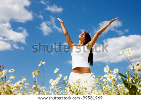 Young woman holding hands high up enjoying the warm sunny day - stock photo