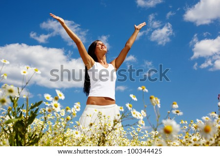 Young woman holding hands high up while enjoying the warm sunny day - stock photo