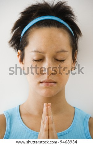 Young woman holding hands in prayer position with eyes closed meditating. - stock photo