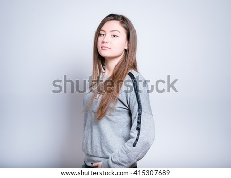 young woman holding hands in the pockets of jeans, close-up isolation on gray - stock photo