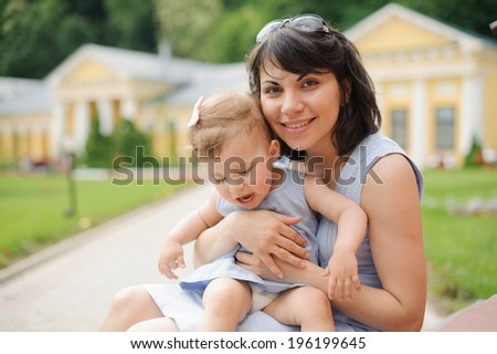 young woman holding her daughter on lap - stock photo