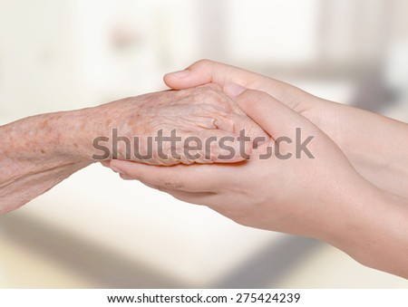 Young woman holding her grandma hand in bedroom - stock photo