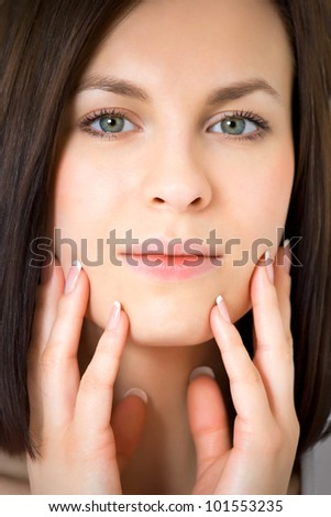 Young woman holding her hands against her face - stock photo