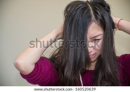 Young woman holding her head looking frustrated - stock photo