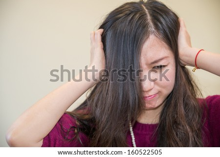 Young woman holding her head looking frustrated