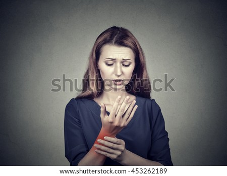 Young woman holding her painful wrist isolated on gray wall background. Sprain pain location indicated by red spot. Negative face expression - stock photo
