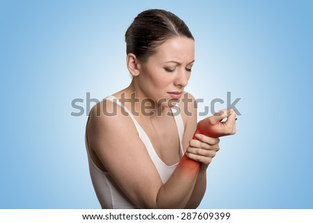 Young woman holding her painful wrist over blue background. Sprain pain location indicated by red spot. - stock photo